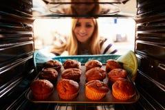 Vrouw die Tray Of Baked Muffins Out van de Oven nemen royalty-vrije stock foto