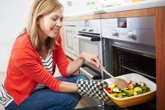 Vrouw die Tray Of Roast Vegetables Into-Oven zetten Stock Fotografie