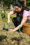 Vrouw die in tuin werkt en hulpmiddelen met behulp van Royalty-vrije Stock Afbeeldingen