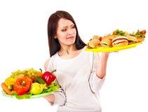 Vrouw die tussen fruit en hamburger kiest. stock fotografie