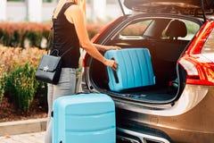 Vrouw die twee blauwe plastic koffers laden aan autoboomstam royalty-vrije stock foto's