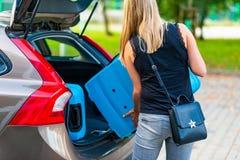 Vrouw die twee blauwe plastic koffers laden aan autoboomstam royalty-vrije stock foto