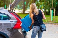 Vrouw die twee blauwe plastic koffers laden aan autoboomstam stock foto's
