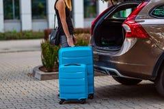 Vrouw die twee blauwe plastic koffers zetten aan autoboomstam stock foto's