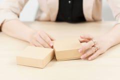 Vrouw die twee kartonvakjes op lijst houden Stock Foto's