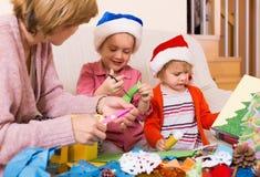 Vrouw die twee meisjes helpen om decoratie voor Kerstmis te maken Stock Foto's