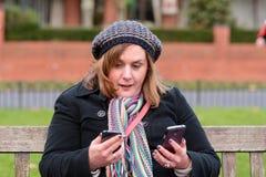 Vrouw die twee mobiele telefoons controleren Stock Fotografie