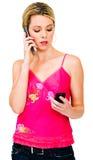Vrouw die twee mobiele telefoons met behulp van stock afbeelding