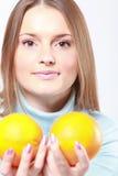 Vrouw die twee oranje vruchten houdt Royalty-vrije Stock Foto