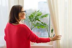 Vrouw die uit het venster die de gordijnen, mening van de rug openen kijken royalty-vrije stock afbeeldingen