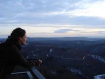 Vrouw die uit het vooruitzicht aan het landschap schemer bekijken stock foto's