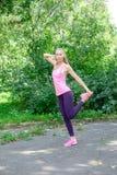 Vrouw die uitrekkende oefening in park doen royalty-vrije stock afbeelding
