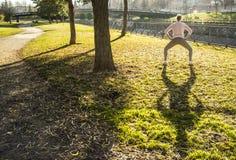 Vrouw die uitrekkende oefeningen doen bij stedelijk park in de herfstseizoen royalty-vrije stock foto's