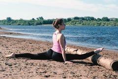 Vrouw die uitrekkende zitting op streng in het zandige strand doen bij zonsondergang royalty-vrije stock foto
