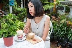 Vrouw die van de koffie en aardbeikleinigheid genieten Royalty-vrije Stock Afbeelding