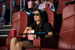 Vrouw die van een 3d film met popcorn genieten Stock Foto's