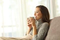 Vrouw die van een kop van koffie in de winter thuis genieten royalty-vrije stock foto's