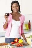 Vrouw die van Glas Wijn in Keuken geniet Royalty-vrije Stock Foto's