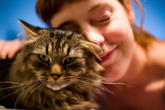 Vrouw die van haar huisdierenkat houdt Stock Foto's