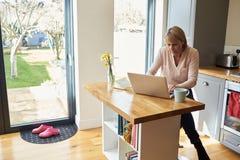 Vrouw die van Huis aan Laptop in Moderne Flat werken royalty-vrije stock afbeeldingen
