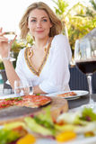Vrouw die van Maaltijd in Openluchtrestaurant genieten Stock Afbeeldingen