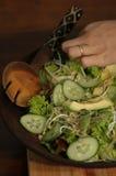 Vrouw die van saladekom eet op lijst Stock Foto's