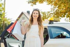 Vrouw die van Taxiauto dragende het winkelen zakken weggaan royalty-vrije stock afbeelding