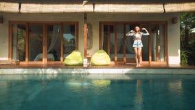 Vrouw die van villa aan zwembad opstappen stock videobeelden