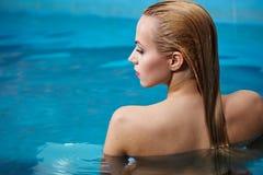 Vrouw die van water in het zwembad genieten Royalty-vrije Stock Afbeeldingen
