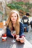 Vrouw die van wijn in het restaurantterras van de stadsstraat genieten Wijn het proeven de zitting van het toeristenmeisje bij de stock afbeeldingen