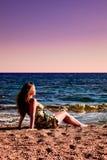 Vrouw die van zonsondergang geniet bij strand Stock Foto