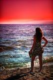Vrouw die van zonsondergang geniet bij strand Royalty-vrije Stock Foto