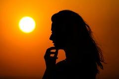 Vrouw die van zonsondergang genieten stock fotografie