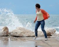 Vrouw die vanaf de golven lopen royalty-vrije stock afbeeldingen