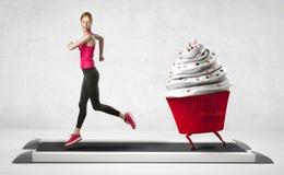 Vrouw die vanaf een cupcake lopen stock foto