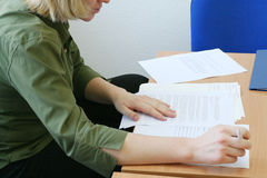 Vrouw die vastbesloten de documenten leest Stock Afbeeldingen