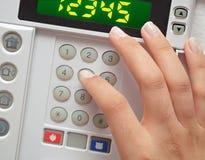 Vrouw die veiligheidscode ingaan aan alarmsysteem Stock Foto's