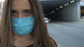 Vrouw die veiligheidsmasker op stadsstraat zetten, milieuvervuiling, epidemie stock videobeelden