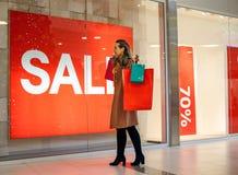 Vrouw die vensterwinkel bekijken - Verkoop in klerenwinkel Stock Fotografie