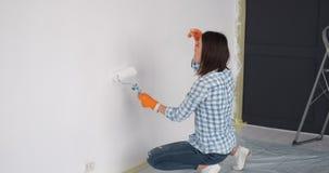 Vrouw die verf op binnenlandse muur met een rol toepassen stock videobeelden