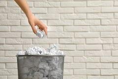 Vrouw die verfrommeld document werpen in metaalbak tegen bakstenen muur, close-up stock foto's