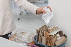 Vrouw die verfrommeld document zetten in afvalbak in bureau Het recycling van het afval stock afbeeldingen
