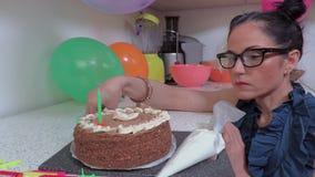Vrouw die verjaardagscake met kaarsen verfraaien stock footage