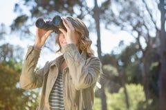 Vrouw die verrekijkers met behulp van Stock Foto