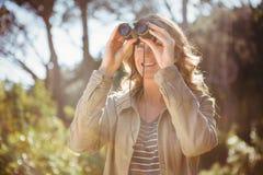 Vrouw die verrekijkers met behulp van Stock Fotografie
