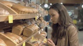Vrouw die vers brood in een supermarkt kopen stock video