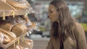 Vrouw die vers brood in een supermarkt kopen stock videobeelden