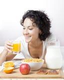 Vrouw die vers jus d'orange voor gezond ontbijt op wit drinken Royalty-vrije Stock Fotografie