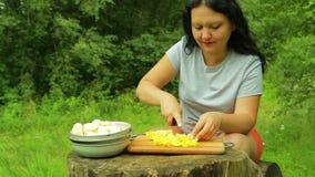 Vrouw die vers oranje fruit met plakken op een houten saladeraad snijden voor een picknick stock footage