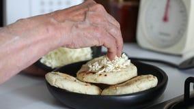 Vrouw die verscheurde kaas toevoegen aan een geroosterde arepa stock footage